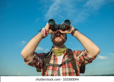 Young smilimg caucasian tourist with backpack  standing on the top of hill against blue sky background and looking through binoculars