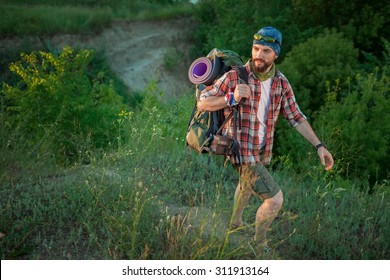 Young smilimg caucasian tourist with backpack walking on the top of hill