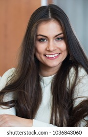 Young smiling  adult girl in white sweater at living room