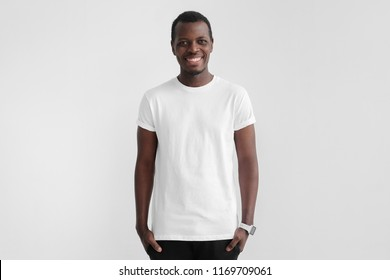 Young smiling african man with dark skin standing with hands in pockets, wearing blank white t shirt with copy space for your logo or text, isolated on gray background