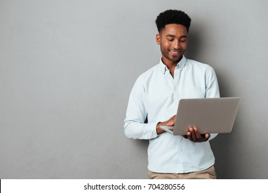 Young smiling african man standing and using laptop computer isolated over gray background