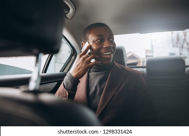 Young smiling african man using smartphone while sitting on backseat in car. Concept of happy business people traveling.