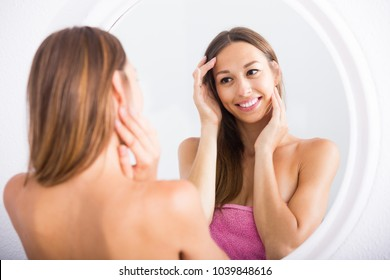 young smiling american woman examining her face by looking at it in mirror