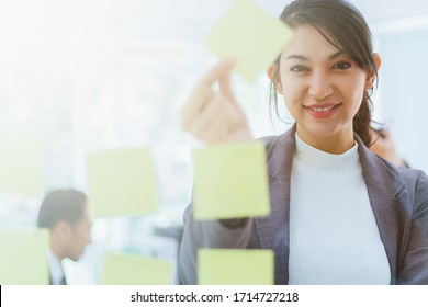 Young smiling asian business woman mentor leader write tasks creative ideas on sticky post it notes on glass wall. businesswoman coach planning project corporate management on sticker scrum board.