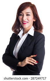 Young smiling asian business woman in suit looking at camera, crossed arms, isolated on white background