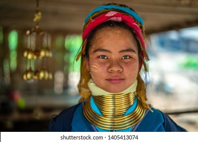 Young smiling Asian long-neck Kayan Padaung woman in traditional costume. Ethnic minority in Asia. Beautiful portrait of tribal woman with neck rings brass coils in Loikaw, Myanmar.