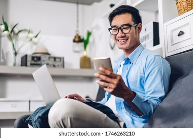 Young smiling asian man relaxing using laptop computer working and video conference meeting at home.Young creative man looking at screen typing message with smartphone.work from home concept