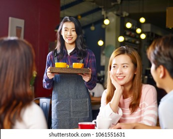 young smiling asian waitress serving customers in coffee shop, focus on the background girl.