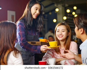 young smiling asian waitress serving coffee to customers.