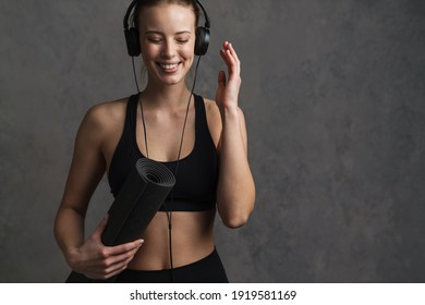Young smiling athletic woman in wireless headphones and sportswear holding fitness mat isolated