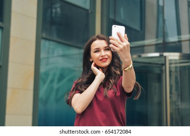 young smiling attractive beauty brunette girl making selfie outdoor