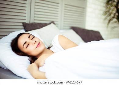 Young smiling attractive brunette woman sleeping in white bed