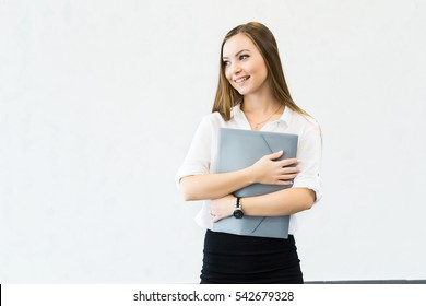 Young smiling attractive business woman isolated on white background holds folder for documents and looking left on copy space.