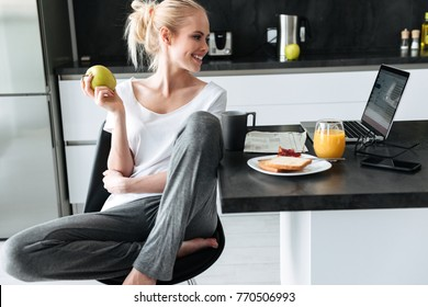 Young smiling attractive lady eating apple and using laptop computer in kitchen while have breakfast