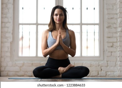 Young smiling attractive sporty woman practicing yoga, doing Ardha Padmasana exercise, meditating in Half Lotus pose with namaste, working out, wearing sportswear, indoor full length, yoga studio