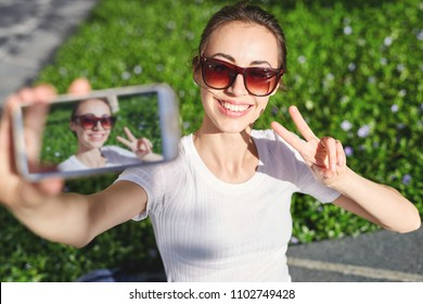 young smiling attractive woman in white t-shirt makes selfie on smartphone at sunny day on the green grass background. woman posing in park.