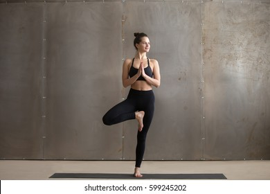 Young smiling attractive yogi woman practicing yoga, standing in Vrksasana exercise, Tree pose, working out, wearing black sportswear, cool urban style, full length, grey studio background