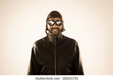Young smiling aviator with vintage glasses and hat wearing leather jacket - isolated on white