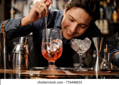 Young smiling barman stirring fresh alcoholic cocktail with sweet fruit syrups on the bar counter