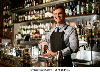 young smiling bartender in black apron preparing to make cocktail. Shelves with bottles of alcohol in background.