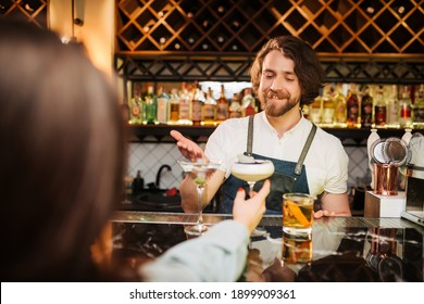 young smiling bartender in black apron preparing to make cocktail. Shelves with bottles of alcohol in background