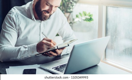 Young smiling bearded businessman in white shirt sitting at desk in front of laptop, making notes in notebook. Freelancer works remotely. Student learning online. Online traning, marketing, education.