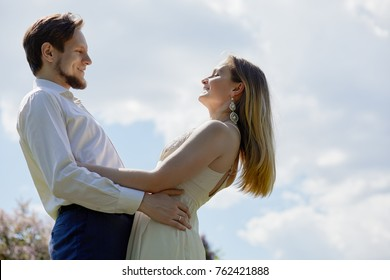 Young smiling bearded man and woman stand looking at each other against cloudy sky.
