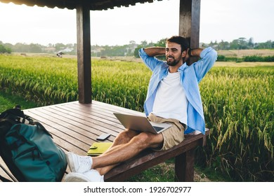 Young smiling bearded remote employee with netbook and hands behind head sitting with crossed legs in pavilion while looking away in summer