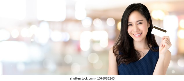 Young smiling beautiful Asian woman presenting credit card in hand, showing trust and confidence for making payment, on panoramic banner bokeh  background with copy space