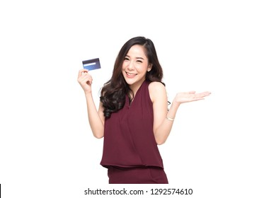 Young smiling beautiful Asian woman presenting credit card in hand for making payment shopping isolated on white background