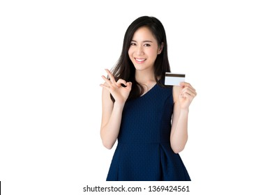 Young smiling beautiful Asian woman showing credit card with okey gesture isolated on white background
