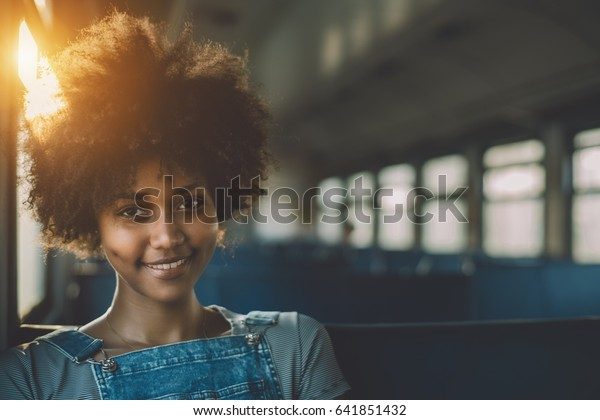 Young smiling beautiful black girl with curly afro hair sitting goes by suburban train, attractive mixed teenage female on seat of empty electrical train with area for your text message or logo