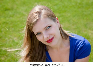 young smiling beautiful blonde girl sitting on the grass in the summer