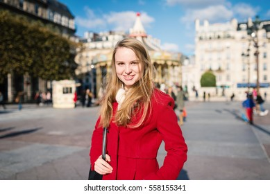 Young smiling beautiful blonde woman portrait in Hotel de Ville square with carousel in the background. Paris, France.