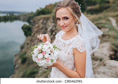 A young smiling and beautiful bride in a white dress is standing against a background of rocks, cliffs and stones. Wedding portrait of a cute curly blonde with a bouquet.