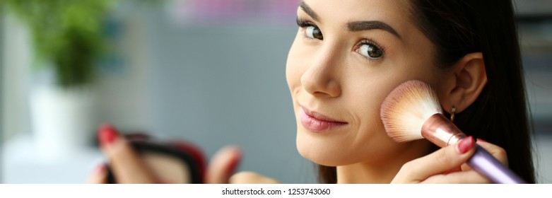 Young smiling beautiful brunette woman make her face up with brush and powder putting rouge in mua office portrait