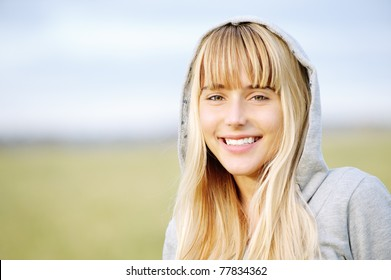 Young smiling beautiful girl in jacket with hood against autumn nature.