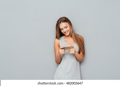 Young smiling beautiful girl typing message on smartphone isolated on a grey background