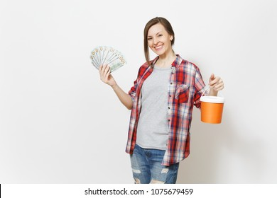 Young smiling beautiful woman in casual clothes holding bundle of dollars, cash money and paint bucket isolated on white background. Instruments for renovation apartment room. Repair home concept