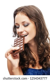 Young smiling beautiful woman with dark hair in blue dress bites off chocolate, isolated on white background.