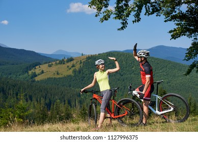 Young smiling bikers couple, man and woman, standing with bikes on grassy hill under big tree having fun with raised hands on fantastic magnificent mountain covered with forest summer background.
