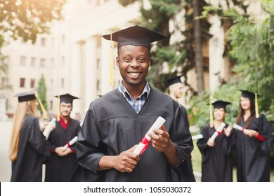Young smiling black male on his graduation day in university standing with multiethnic group of friends. Education, qualification and gown concept.