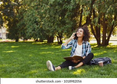 Young smiling black woman reading book in park and talking on phone, preparing for exams at university or college, discussing topic with friend. Education concept, copy space