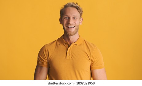 Young smiling blond bearded man dressed in casual wear looking happy on camera over colorful background