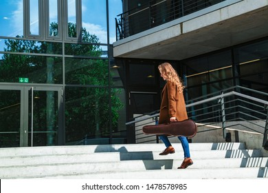 Young smiling blond female student musician in brown coat with violin in leather case climbs the stairs to conservatory lesson or music hall to concert at sunny day. Music, education and art concept