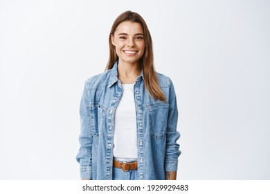 Young smiling blond girl with perfect teeth staring at camera, standing relaxed against white background in casual clothes, lifestyle and emotions concept