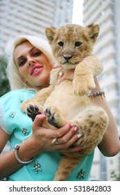Young smiling blonde holds funny calf of lion lies outdoor at summer, focus on animal
