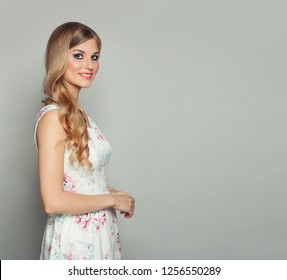 Young smiling blonde model woman in dress on white background
