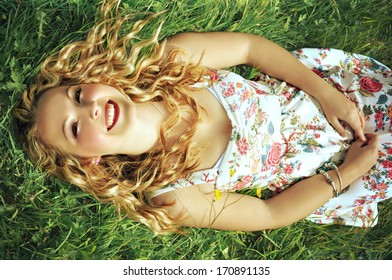 Young smiling blonde woman with red lips and curly hair lying on grass.