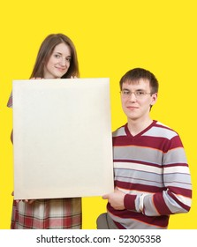Young smiling boy and girl with poster over yellow